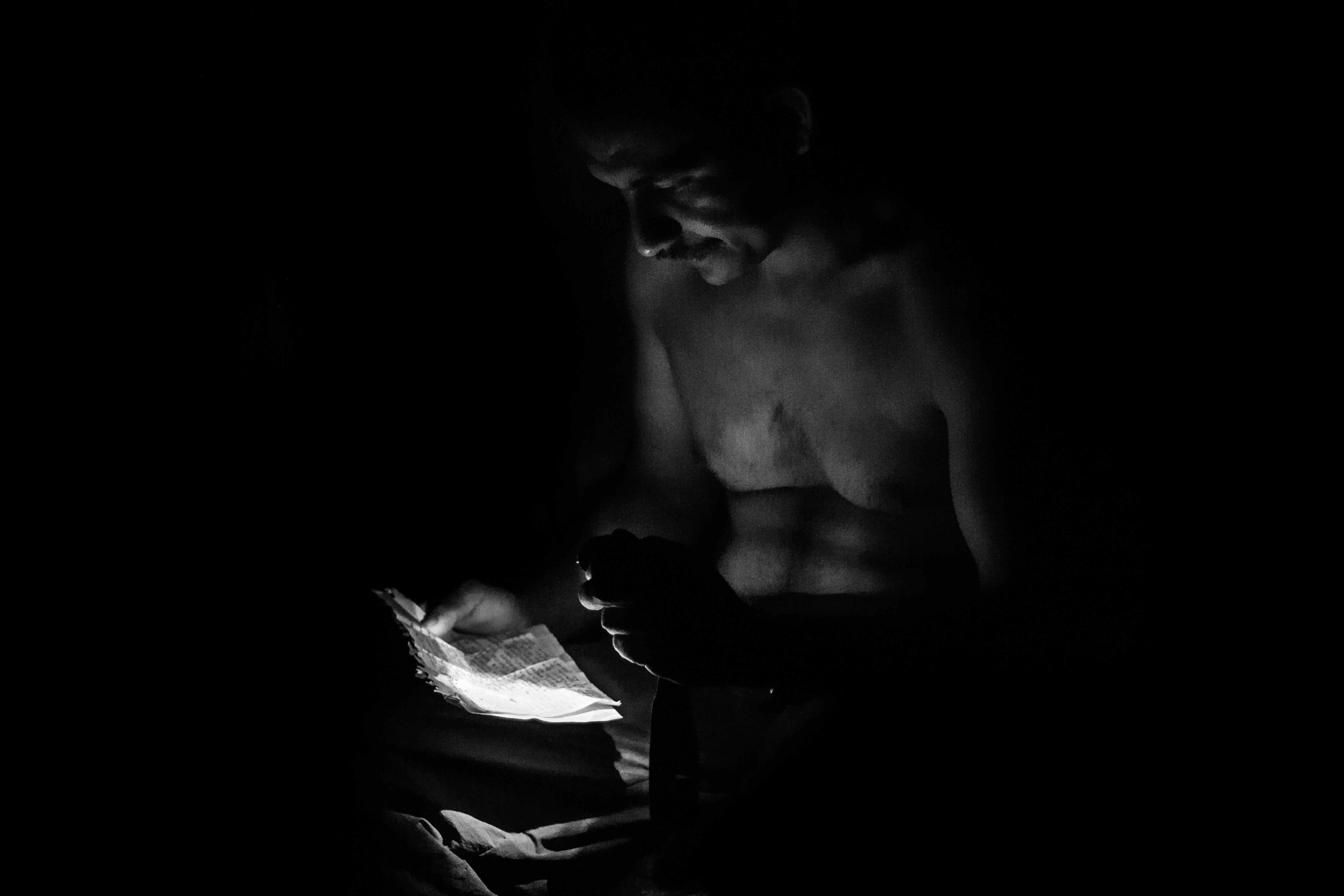 """Jefferson """"gato"""", guerrillero del Frente 15 de las FARC, lee una carta que le ha enviado un familiar. En su caleta solo utiliza una mínima luz roja que deja ver solo un poco su silueta."""